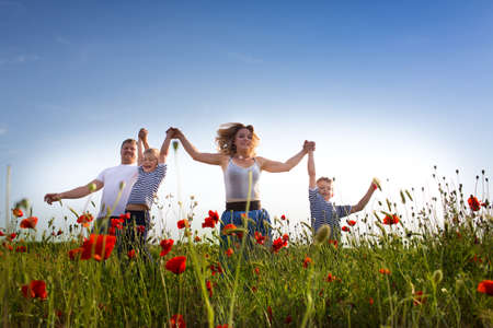 countryside loving: Family of four person playing on the poppy field Stock Photo