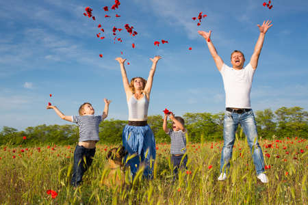 Family of four person playing on the poppy field Stock Photo