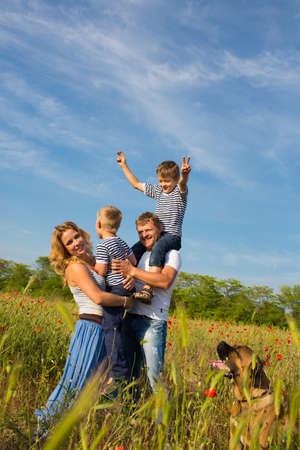 ケシのフィールドでプレー 4 人の家族 写真素材