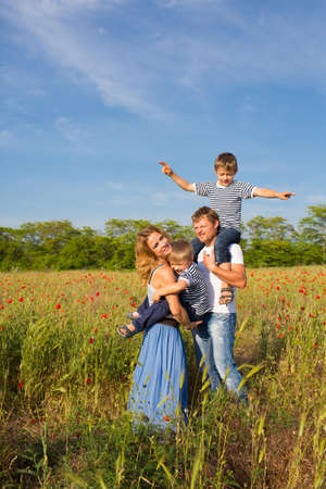 Family of four person playing on the poppy field Zdjęcie Seryjne