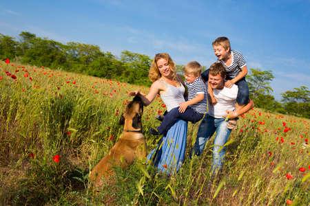 familia jugando: Familia de cuatro personas que juegan en el campo de amapolas