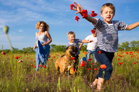 Family of four person playing on the poppy field Standard-Bild