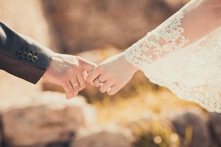 Bruid en bruidegom die zijn handen houdt Stockfoto
