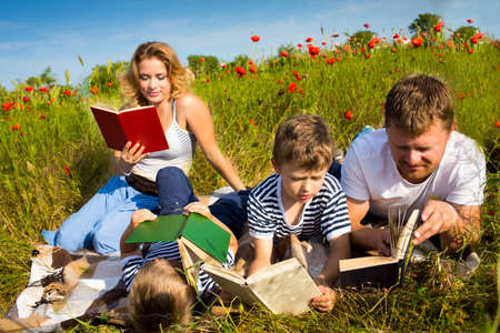 Family reading books laying on the grass