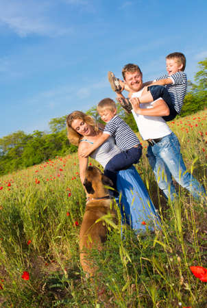 Family of four person and dog playing on the poppy field Banco de Imagens - 20100686