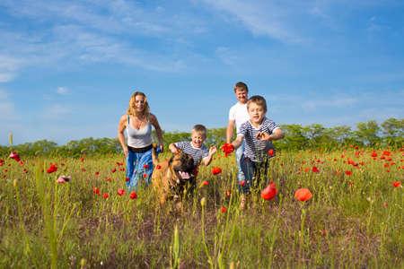 Famiglia di quattro persone e il cane che gioca sul campo di papaveri Archivio Fotografico - 20101034