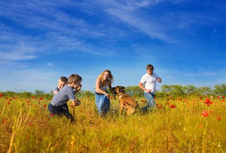 Familia de cuatro personas y un perro jugando en el campo de amapolas