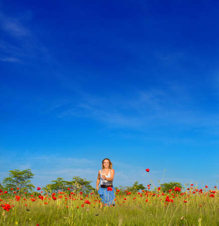 Beautiful young woman running on the poppy field photo