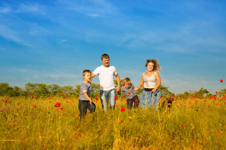 Family of four person and dog playing on the poppy field