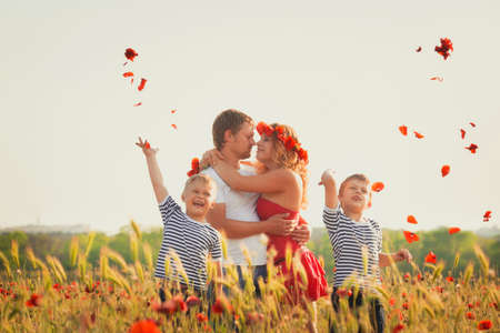 Family of four person playing on the poppy field Stockfoto