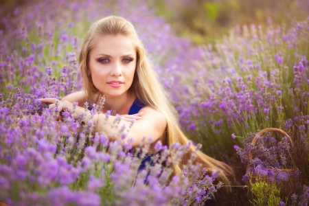 Blond girl with long hair on lavender field Фото со стока