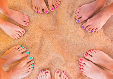 Six pairs of woman feet on the sand
