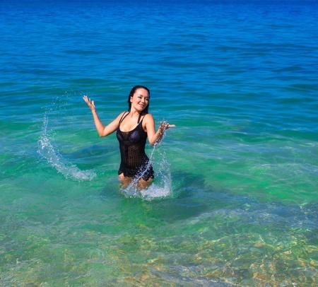 Bella donna che gioca in acqua di mare