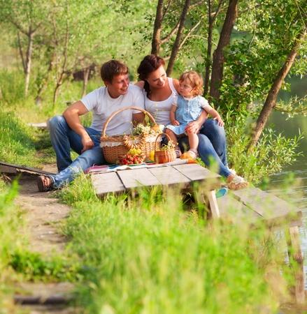 De gelukkige familie heeft picknick op het meer Stockfoto