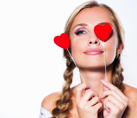 Junge Frau mit Herz-Symbole in den Händen.