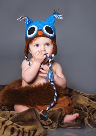 Little boy sitting on the fur in winter hat