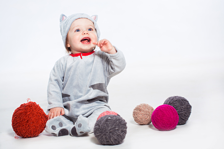 Little boy in cat costume playing with balls of wool