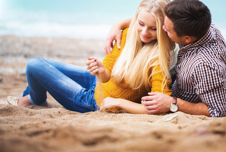Couple relaxing on the autumn beach