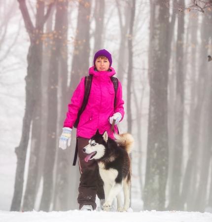 Beautiful girl walking with husky dog