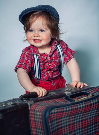 Little boy standing near old suitcase Banco de Imagens