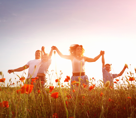 Happy family playing on the poppy meadow