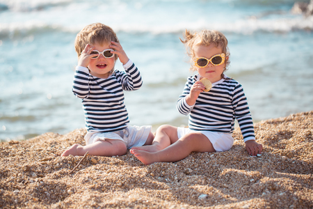 Little boy and girl playing on the beach Banco de Imagens