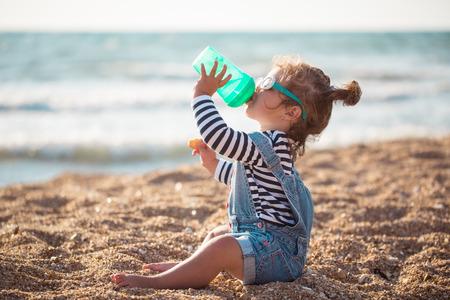 Meisje drinkwater op het strand