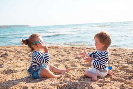 Little boy and girl playing on the beach Imagens