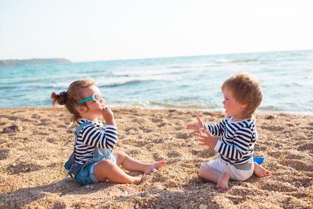 Weinig jongen en meisje spelen op het strand