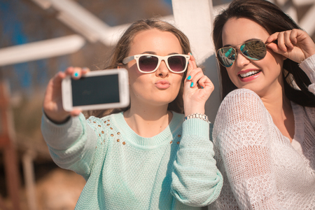 Young beautiful girls taking self photo by cellphone Imagens