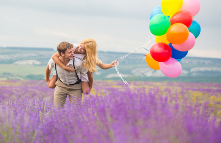 Happy young couple person walking on lavender field with color air balloons