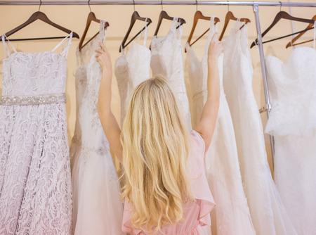Beautiful young woman  selecting evening dress