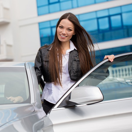 Portrait of beautiful young woman near the new car - outdoors