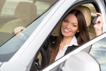 Portrait of beautiful young woman in the new car - outdoors Imagens
