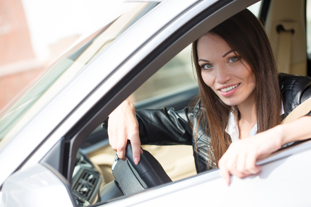 Portrait of beautiful young woman in the new car - outdoors