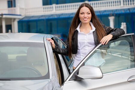 Portrait of beautiful young woman near the new car - outdoors Imagens