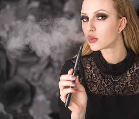 Luxurious blonde in an evening dress smokes an electronic cigarette on a black background