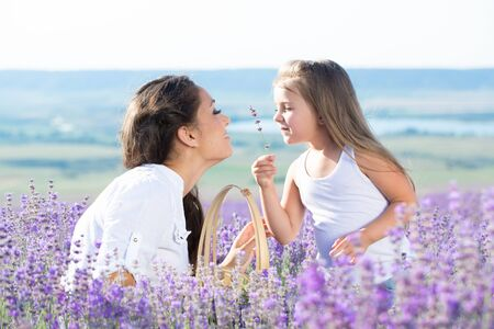 Beautiful happy couple mother and her cute daughter in lavender field