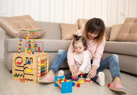 Moeder en dochter die binnen spelen houten speelgoed