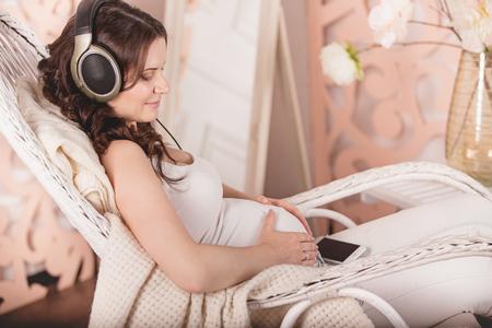 임신 한 여자 집에서 헤드폰에서 음악을 듣고의 초상화.