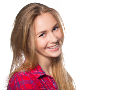 Close up portrait of smiling teen girl showing dental braces. Isolated on white background. Фото со стока