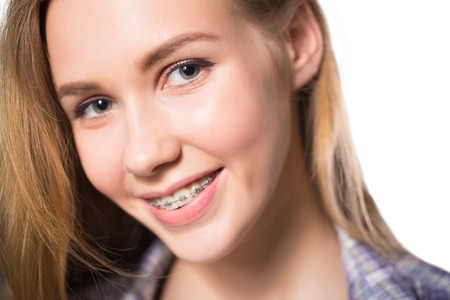 Close up portrait of smiling teen girl showing dental braces. Isolated on white background. Standard-Bild