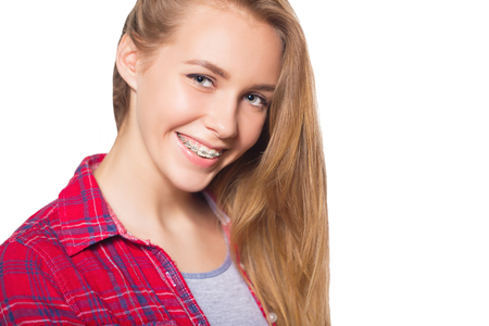 Close up portrait of smiling teen girl showing dental braces. Isolated on white background. Banco de Imagens