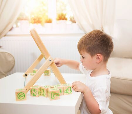 Little boy playing with abacus toy at home Banco de Imagens