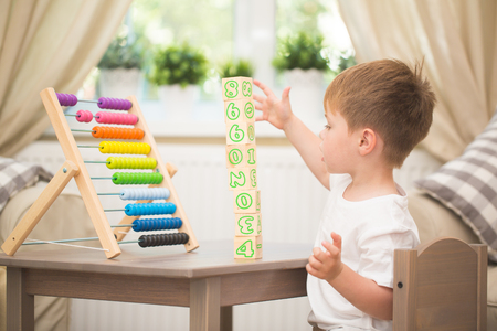 Little boy playing with abacus toy at home Stock Photo