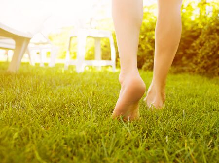 Close up female crossed legs walking on the grass in a park. Stockfoto