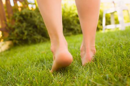 Close-up vrouwelijke gekruiste benen lopen op het gras in een park.