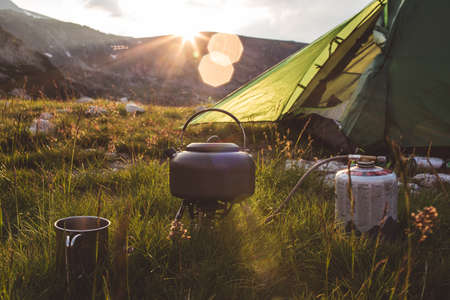 Camping teapot and cap on the gras at sunrise time. Mountains of Bulgaria.
