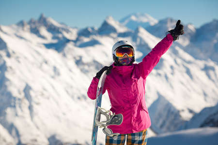 Female snowboarder in the alpine mountains