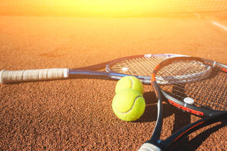 Tennis balls and racket on the court Stock Photo